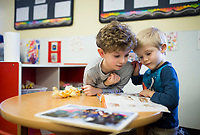 NWA Democrat-Gazette/CHARLIE KAIJO Trey Crouch, 5 (from left), and Whitten Smith, 5, look at a  magazine, Monday, February 12, 2018 at Helen R. Walton Children&acirc;&euro;&trade;s Enrichment Center in Bentonville. <br />