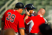 Jacob May (20) of the Kannapolis Intimidators has his lip checked out by trainer Cory Barton (right) as Kannapolis Intimidators manager Tommy Thompson (39) looks on during the game against the West Virginia Power at CMC-Northeast Stadium on July 9, 2013 in Kannapolis, North Carolina.  The Power defeated the Intimidators 3-1.   (Brian Westerholt/Four Seam Images)