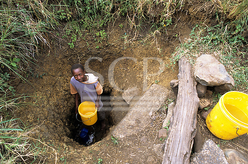 Lolgorian, Kenya. Girl collecting water from a nearly dry open well.