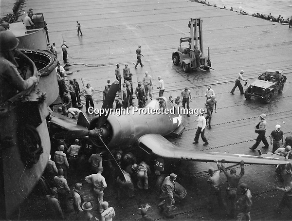 After having a shell hole in his fusilage behind the cockpit, Lt. Reed crash landed a F4U Corsair. The tail hook and back of plane ripped off and remained at the end of deck, while the rest of plane raced down the flight deck and a wing crashed into a gun turret. - July 24, 1945