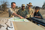African Lion (Panthera leo) biologists, Luke Hunter, Jake Overton, and Kim Young-Overton, discussing poaching activities with park scout, Timbo Frackson, Kafue National Park, Zambia