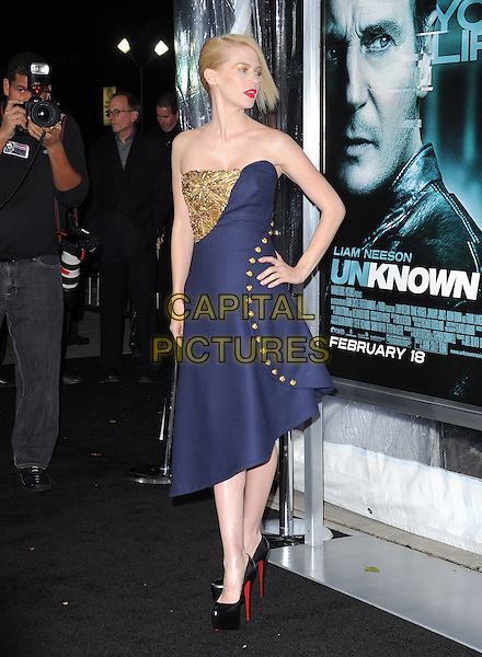 """JANUARY JONES .Premiere of """"Unknown"""" held at The Regency Village Theatre in Westwood, California, USA..February 16th, 2011.full length navy blue strapless gold beads beaded embellished jewel encrusted dress hand on hip black platform shoes .CAP/RKE/DVS.©DVS/RockinExposures/Capital Pictures."""