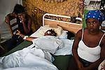 Une femme amputée d'un bras est veillée par ses proches dans les jardins de l'hôpital St Pierre à Jacmel (Haiti) le 19/01/2010. Partiellement détruit par le séisme du 12/01/2010, il héberge plus de 60 patients, certains atteints de gangrène faute de soins adéquats.