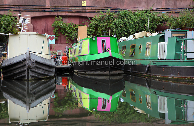 Canal Boats on permanent mooring, Regent's Canal, London, UK. Regent's Canal links the Paddington arm of the Grand Union Canal; just north-west of Paddington Basin in the west; to the Limehouse Basin and the River Thames in east London. It was built by John Nash (architect) and James Morgan (engineer) and opened in two stages, from Paddington to Camden in 1816, and the rest of the canal in 1820. Picture by Manuel Cohen