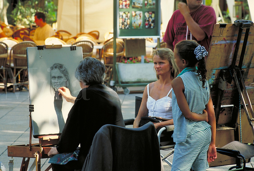 "Bijan Emami does portrait of blond woman from Germany. Artist's """"studio"""" is broad pedestrian esplanade. Black girl with ribbon in ponytail watches intently. Bijan Emami. Avignon Provence France."