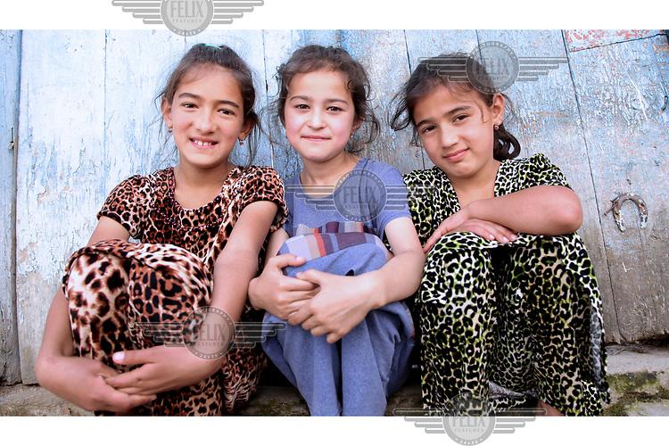 Gulnar sitting between twins Fatima and Zuhra, both 10, in the village of Zimchurud.