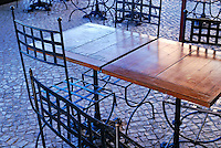 Wrought iron chairs and wooden tables in cafe