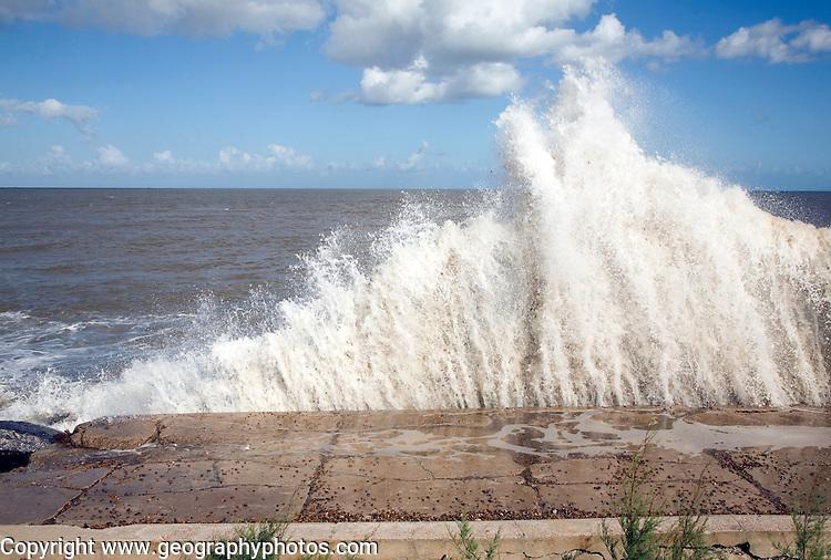 Waves hit sea wall illustrating hydraulic action and corrasion coastal erosion, East Lane, Bawdsey, Suffolk