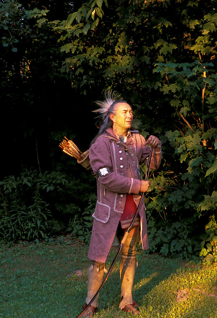 Late 1700's Shawnee re-enactor, Roger Moore, dressed in traditional Shawnee clothing of a frock jacket, leather leggings and silver arm bands holds a traditional wooden bow that would have been used for hunting and warfare. Surroundings are the wooded homelands of the Shawnee Indians in the Ohio Valley, Ohio. Model released