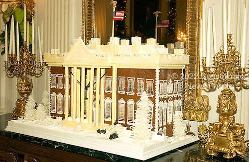 """Washington, D.C. - November 30, 2005 -- Mrs. Laura Bush announced """"All Things Bright and Beautiful"""" as the theme for the 2005 holiday season at the White House in Washington, D.C. on November 30, 2005.  This is the traditional gingerbread White House displayed in the State Dining Room.  It was designed by Thaddeus DuBois, the White House pastry chef.  It depicts the north side of the White House as it looks today.  The gingerbread house consists of 100 pounds (34 sheets) of gingerbread, 150 pounds of white and dark chocolate, Clear, poured sugar windows, and one strand of white lights inside the Gingerbread White House make it glow..Credit: Ron Sachs / CNP"""