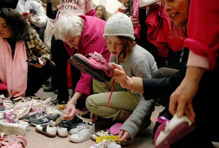 Adina Berliant, 12, of California, reads the name on a pair of shoes that represent Iraqi civilian dead, at a protest in the Hart Building atrium, organized by CODEPINK.