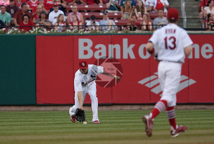 June 19, 2010       St. Louis Cardinals center fielder Colby Rasmus (28) scoops up a ball that blooped through the infield.   At right is St. Louis Cardinals shortstop Brendan Ryan (13).  The St. Louis Cardinals defeated the Oakland Athletics 4-3 in the second game of a three-game homestand at Busch Stadium in downtown St. Louis, MO on Saturday June 19, 2010.
