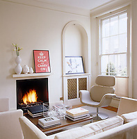 A roaring fire adds a touch of warmth to this white living room