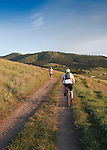 A Bike rider heads up the trail as a runner comes back down on a summer evening in Missoula, Montana