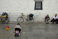 Street scene near Barkhor street, Lhasa, women praying near the Jokhang Temple, Lhasa, Tibet,.The Jokhang Temple is one of Tibet's holiest shrines, originally built in 647 A.D. in celebration of the marriage of the Tang Princess Wencheng and the Tubo King Songtsen Gampo. In front of the gate is a stone Tablet of Unity from the Tang Dynasty; inscribed are both Chinese characters and Tibetan script. Nearby is the stump of the willow tree said to have been planted by Princess Wencheng herself; two younger willow trees now flank the stump of the first tree...Located in the center of old Lhasa, the temple was built by craftsmen from Tibet, China, and Nepal and thus features different architectural styles. The temple is also the spiritual center of Tibet and the holiest destination for all Tibetan Buddhist pilgrims. In the central hall is the Jokhang's oldest and most precious object--a gold statue of a seated 12-year-old Sakyamuni. This is said to have been transported to Tibet by Princess Wencheng from her home in Changan in 700 A.D. Other precious antiques in the temple include a silk portrait of Buddha from the Tang Dynasty and a pearl gown and gold lamp from the Ming Dynasty. The three-leafed roof of the Jokhang offers splendid views of the bustling Barkhor market and across to the Potala Palace..