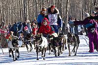 Martin Buser and team run past spectators on the bike/ski trail during the Anchorage ceremonial start during the 2014 Iditarod race.<br /> Photo by Britt Coon/IditarodPhotos.com