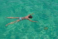 Woman snorkeling by turquoise sea, Saona Island, Dominican Republic