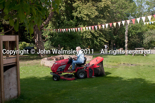 Cutting the grass, Summerhill School, Leiston, Suffolk. The school was founded by A.S.Neill in 1921 and is run on democratic lines with each person, adult or child, having an equal say.  You don't have to go to lessons if you don't want to but could play all day.  It gets above average GCSE exam results.
