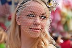 A girl in the New York City Easter Parade wearing a small hat with white flowers and a delicate white net over her face