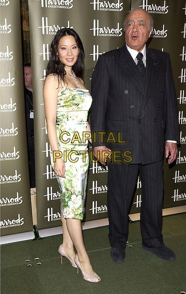 LUCY LIU & MOHAMED AL FAYED.Opens the Harrods January Sale, Harrods, Knightsbridge, London, January 3rd 2005..full length green blue brown floral patterned dress flower print printed peep toe shoes holding hands.Ref: DH.www.capitalpictures.com.sales@capitalpictures.com.©David Hitchens/Capital Pictures .