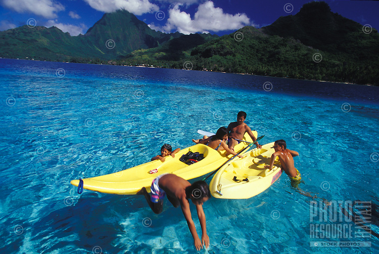 Kids and adult playing in kayaks in clear blue waters of Moorea lagoon, motu islet in background