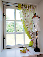 A bedroom window is adorned with homemade floral print curtains