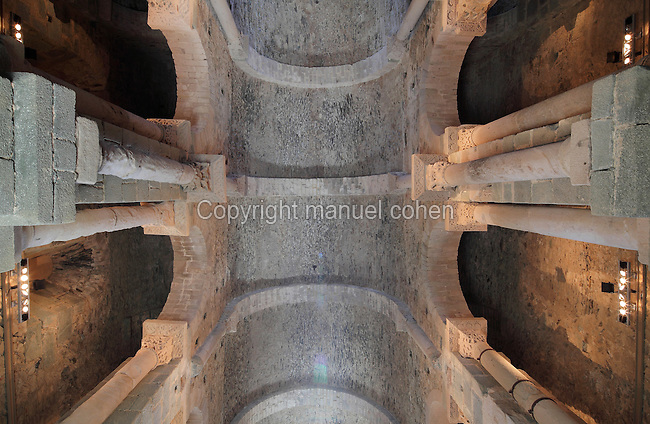 Looking up at the ceiling of the nave of the Romanesque church, founded 1022, of Sant Pere de Rodes, a Benedictine monastery on the Verdera mountain in the Sierra de Rodes, Puerto de la Selva, Girona, Catalonia, Spain. The columns have been reused and the capitals show Corinthian influence. The church displays influences of Carolingian, Pre-Romanesque and Roman architecture and is one of the most important Romanesque structures in Catalonia. The monastery itself was founded in 945 by monks who escaped Barbarian invasions with relics of saints, and was eventually sacked in the 17th century and deserted in the 18th century. Picture by Manuel Cohen