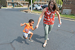 Three-year old Youel, a resettled refugee from Eritrea, hangs on to the hand of Erin Chesson, an employment specialist with Church World Service, as they walk to a playground in Durham, North Carolina. <br /> <br /> The boy and his mother were resettled in Durham by Church World Service, which resettles refugees in North Carolina and throughout the United States.<br /> <br /> <br /> Photo by Paul Jeffrey for Church World Service.