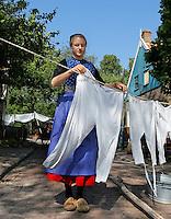 Het Zuiderzeemuseum in Enkhuizen brengt de verhalen tot leven van mensen die vroeger rond de Zuiderzee woonden.  Het museum richt zich op de geschiedenis, actualiteit en toekomst van het gebied. De thema's water, ambacht en gemeenschappen staan centraal. Jonge vrouw uit Urk hangt de was op