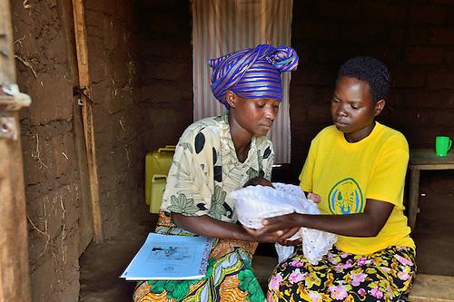 Community Health Worker Marie Chantal examines r three-week old newborn, and talks to the mother,  in Batamuliza Hururiro village, near Rukumo Health Center, Rwanda