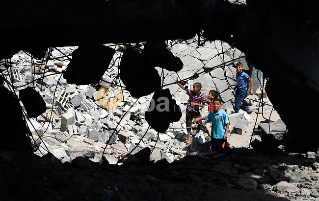 Palestinian boys searche in the rubble of the heavily damaged al-Faruq mosque which was destroyed by Israeli strikes during the summer's fierce offensive, in Rafah in the southern Gaza Strip September 21, 2014. Photo by Abed Rahim Khatib
