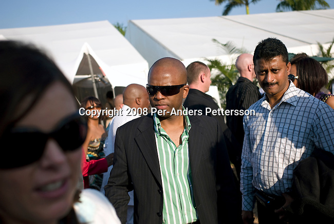 DURBAN, SOUTH AFRICA - JULY 5: Sandile Zungu (c), age 41, talks to friends as he attends the annual Durban July horse race on July 5, 2008, in Durban, South Africa. It?s the biggest social event of the winter season and people from all over the country come to dress up and party. Many of South Africa?s big companies host lavish parties and receptions for VIP clients. Known as a whiz kid, Mr. Zungu runs ZICO, his own investment company, and he has made millions rands of black empowerment deals in the country. He is an outspoken critic of the ANC regime. He is also a supporter of Jacob Zuma, the ANC leader, and the next inline to become president of South Africa in the general elections on April 22, 2009. (Photo by: Per-Anders Pettersson/Getty Images)..