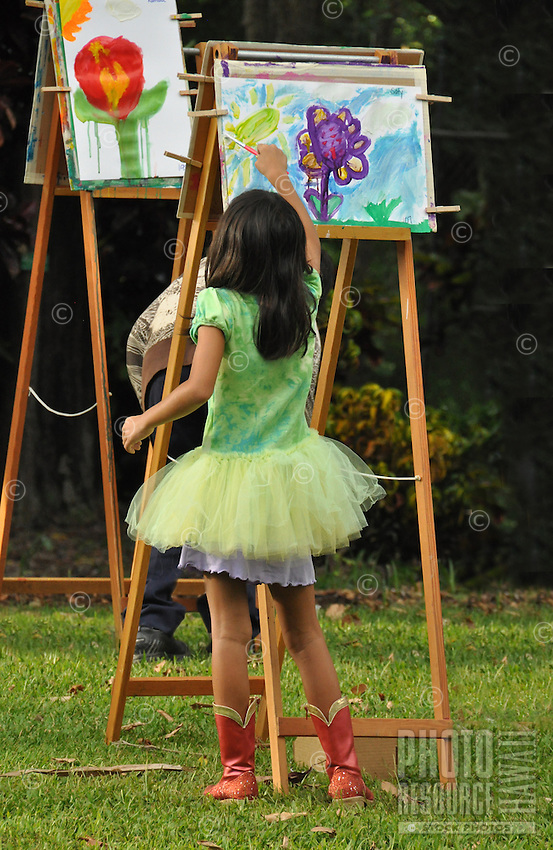 A young girl wearing a tutu and cowboy boots paints a flower picture at Foster Botanical Garden's Midsummer Night's Gleam festival, Honolulu, O'ahu.