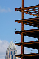 The steel frame of a new high rise grows alongside Charlotte's Bank of America headquarters.