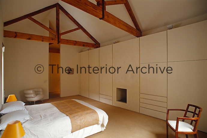 The bedroom has a wall of built-in cupboards around a minimalist fireplace and the wooden roof beams have been kept as an architectural feature