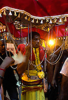 man carrying kavari   at Thaipusam ceremonies,  Batu Caves, Kuala Lumpur, Malaysia, 2012. Thaipusam ceremonies, celebrated by tamile Hindu community in Malaysia, take place  in Sanctuary of Batu Caves at the border of Kuala Lumpur, each year around end of January or beginning of February, according to Hindu moon calendar. The event is paying hommage to Lord Murugan, a spirit or god created by Shiva to lead the army of gods against the army of evil demons, finally defeating the evil spirits. There are many ways to present offerings or sacrifices for this major religious event. Devotees mortify their bodies by carrying heavy kavaris with spears fixed in their skin or fruits, flowers and little post with holy milk fixed with hooks in their skin, ascending the stairways to the sanctuary in trance, `followed by assistant  taking care and musicians playing loud and fast rhythmic trance music.  Many families shave their head in a ritual before ascending the stairways, as part of rituals to obtain salvation for their ancestors.