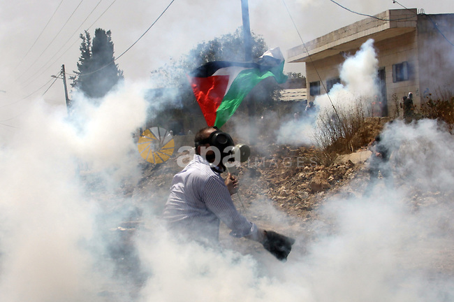 A Palestinian Protester returns a teargas towards Israeli soldiers during clashes in the northern West Bank village of Kufr Qaddum, after the weekly protest against the expansion of the nearby Jewish settlement of Kdumim, on May 25, 2012. Photo by Nedal Eshtayah