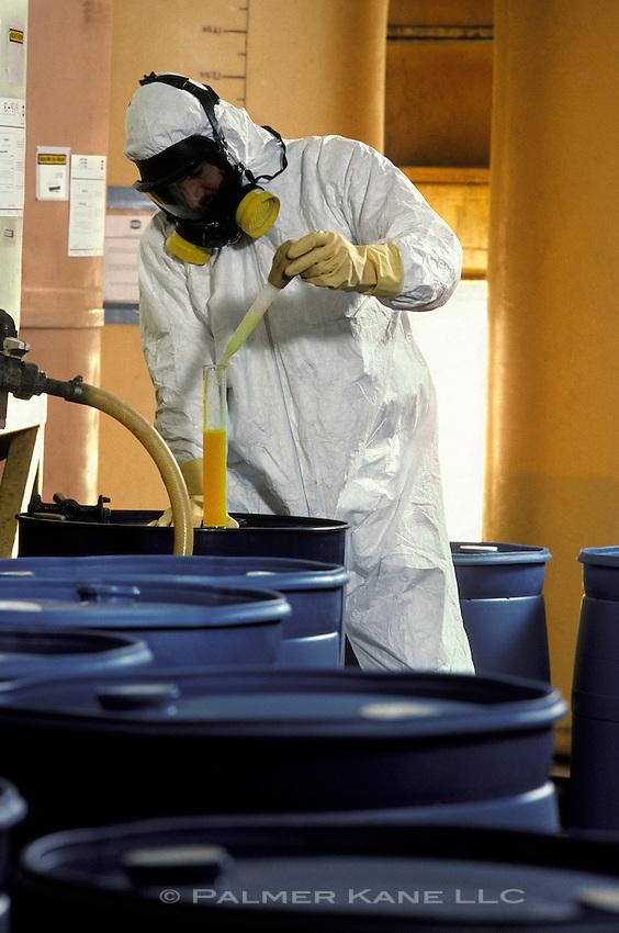 Hazardous material warehouse worker taking sample