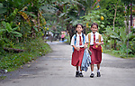 "Two girls walk to school in Tugala, a village on the Indonesian island of Nias. The village was struck by both a 2004 tsunami and a 2005 earthquake, leaving houses destroyed and lives disrupted. The ACT Alliance helped villagers here to construct new homes and latrines, build a potable water system, open a clinic and schools and get their lives going once again. For the residents of Tugala, the post-disaster mantra of ""build back better"" became a reality with help from the ACT Alliance."
