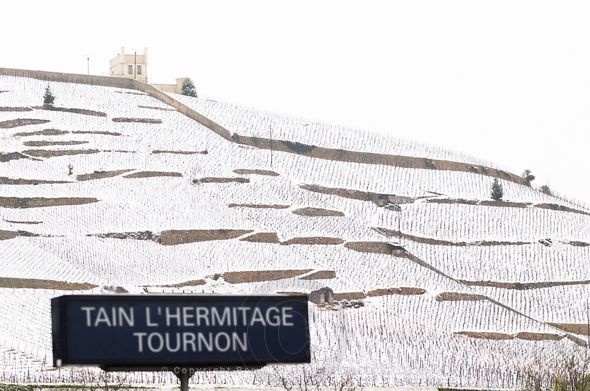 The Maison Blanche White House vineyard and the sign at the railway station for Tain l'Hermitage Tournon. Vineyard in focus. The Hermitage vineyards on the hill behind the city Tain-l'Hermitage, on the steep sloping hill, stone terraced. Sometimes spelled Ermitage. Vineyards under snow in seasonably exceptional weather in April 2005. Tain l'Hermitage, Drome, Drôme, France, Europe