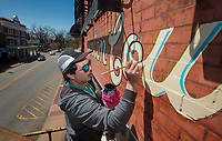 NWA Democrat-Gazette/BEN GOFF @NWABENGOFF<br /> Graham Edwards restores the historical sign reading 'Benton County Hardware Co' Tuesday, April 10, 2018, on the front of the former hardware store on West Central Avenue in downtown Bentonville. Edwards is carefully following the lines of the barely-visible sign on the 1893 building, which is presently home to Fellow Human art gallery, Remedy Road and Simple Machine. Bentonville History Museum and Runway Group partnered to make the project possible.