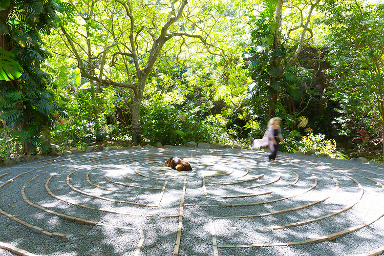 Garden owner Eve Eschner Hogan, with her dog Bodi in the center, walking the labyrinth at the Sacred Garden of Maliko, a garden and nursery at Maliko Gulch near Makawao, Maui, Hawaii, USA