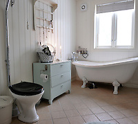 A simple bathroom is furnished with a free-standing slipper bath and a toilet with an old-fashioned cistern
