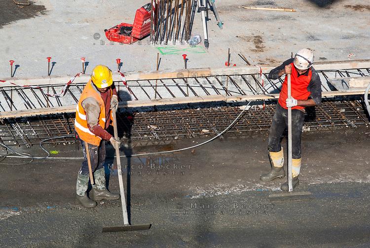 Milano, Lavoratori edili lavorano il cemento --- Milan, construction workers working on cement