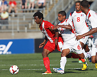 Belize forward Michael Salazar (11) dribbles as Cuban defender Joel Colome (6) closely defends. In CONCACAF Gold Cup Group Stage, the national team of Cuba (white) defeated national team of Belize (red), 4-0, at Rentschler Field, East Hartford, CT on July 16, 2013.