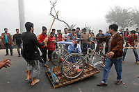 Bangladesh main opposition Bangladesh Nationalist Party activists smash a rickshaw as its driver tries to stop them during a protest in Kachpur, on the outskirts of Dhaka, Bangladesh.