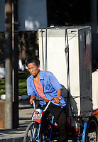 "A man moves a refrigerator by bicycle, Pyongyang, North Korea. The DPRK (Democratic People's Republic of Korea) is the last great dictatorship where the people are bombarded with images of the ""Eternal President"" Kim Il-sung who died in 1994 and his son and current leader Kim Jong-il who are worshipped like a God."