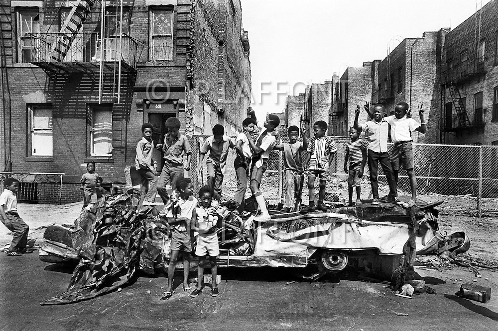 Brooklyn, New York City, NY. August, 1971. <br /> Kids standing on a wreck on a very hot summer day in Bedford Stuyvesant. There were poor housing, kids playing on the streets, burnt buildings, abandoned stolen cars, and unemployement.