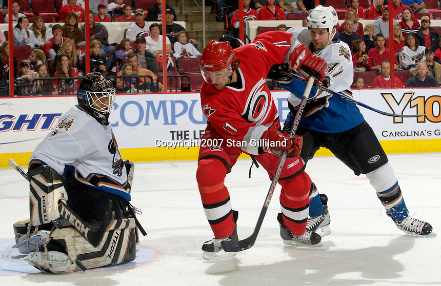 Carolina Hurricanes' Justin Williams looks to follow his shot defended by the Washington Capitals' goalie Brent Johnson and Bryan Muir, right, Thursday, March 22, 2007 at the RBC Center in Raleigh, NC. Carolina won 4-3.