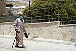 Palestinian man wearing protective mask, walks outside the Ibrahimi mosque, in the midst of the coronavirus COVID-19 outbreak, in the West Bank town of Hebron on June 26, 2020. Photo by Mosab Shawer